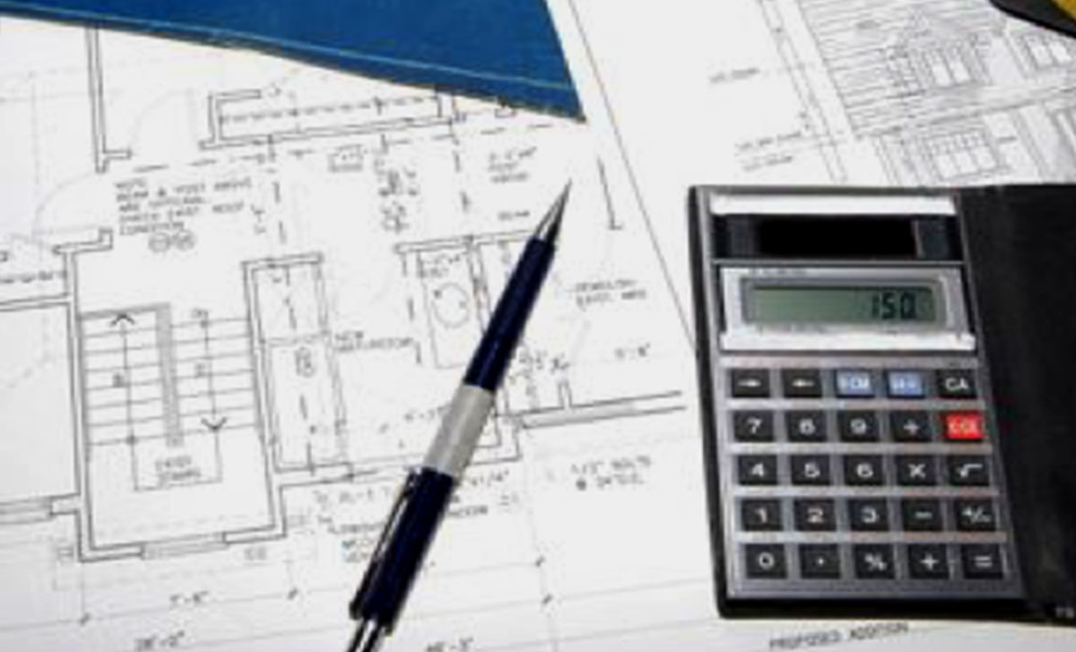 Calculator and pen lay on top of kitchen design plans