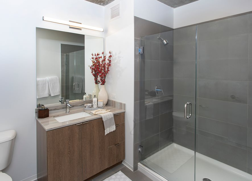 Aspire bathroom with glass shower stall and wooden sink cabinets