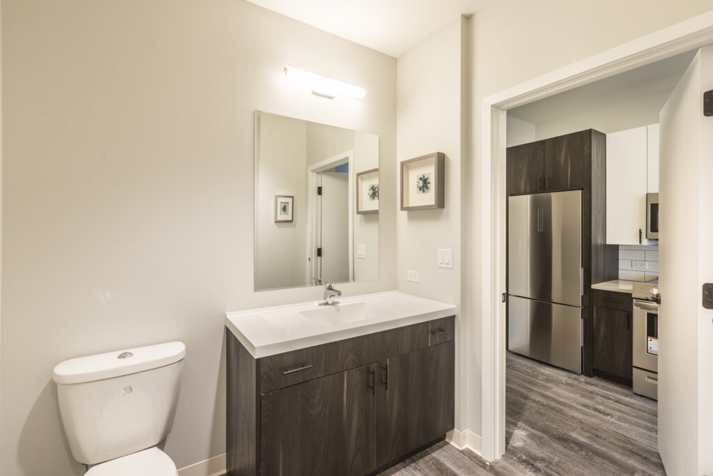 Edge on Broadway bathroom with white sink and countertop, and dark wood grain cabinets
