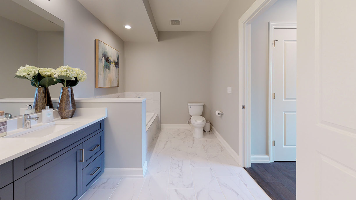 Fox River Crossing bathroom with grey tiled marble floor, white counters, and black cabinets