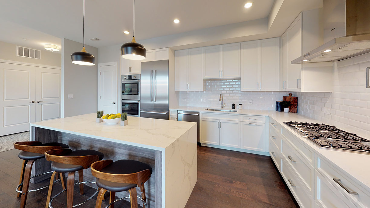 Foxford Station kitchen with white cabinets, white marbled countertops, silver appliances, and dark wooden chairs