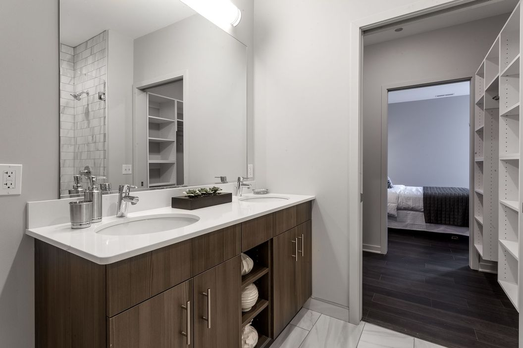 Luxe on Chicago bathroom with white counters, dark wooden cabinets, and grey marbled tiles
