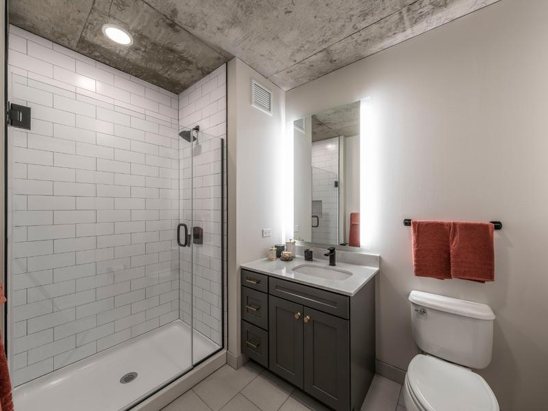 Marlowe bathroom featuring white shower tiles, grey sink cabinets, and grey tiled floor
