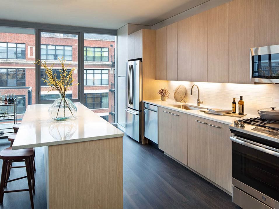 Milieu kitchen with light wooden cabinets, white countertops, silver appliances, dark wooden floor, and white tile backsplash