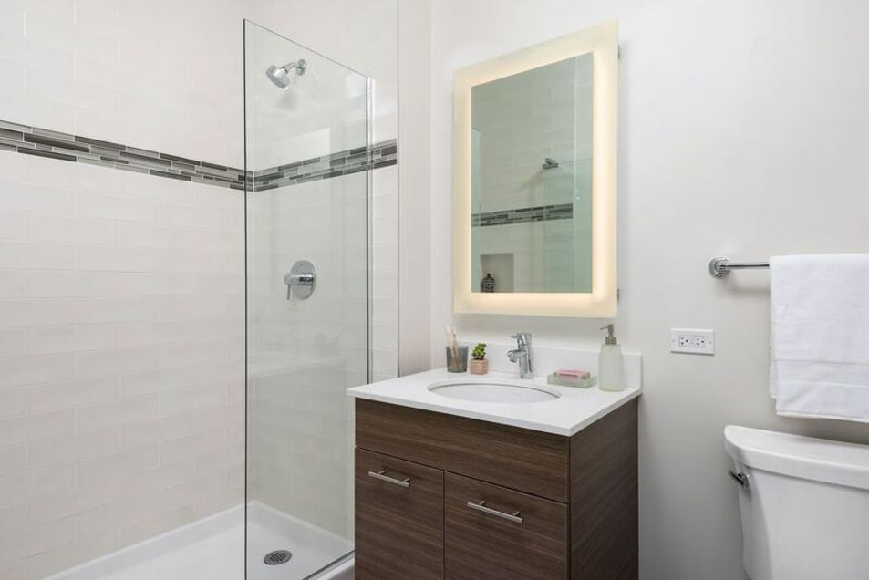Next bathroom with dark brown wooden cabinet, single sink with white counter, glass shower stall with white and grey tiles, and backlit mirror