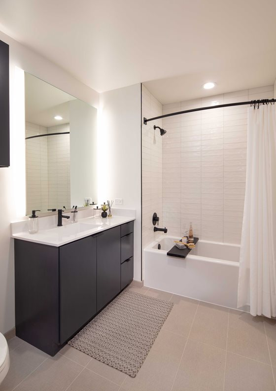 North + Vine bathroom with white countertop, black cabinets, white shower tiles, and tan tiled floor