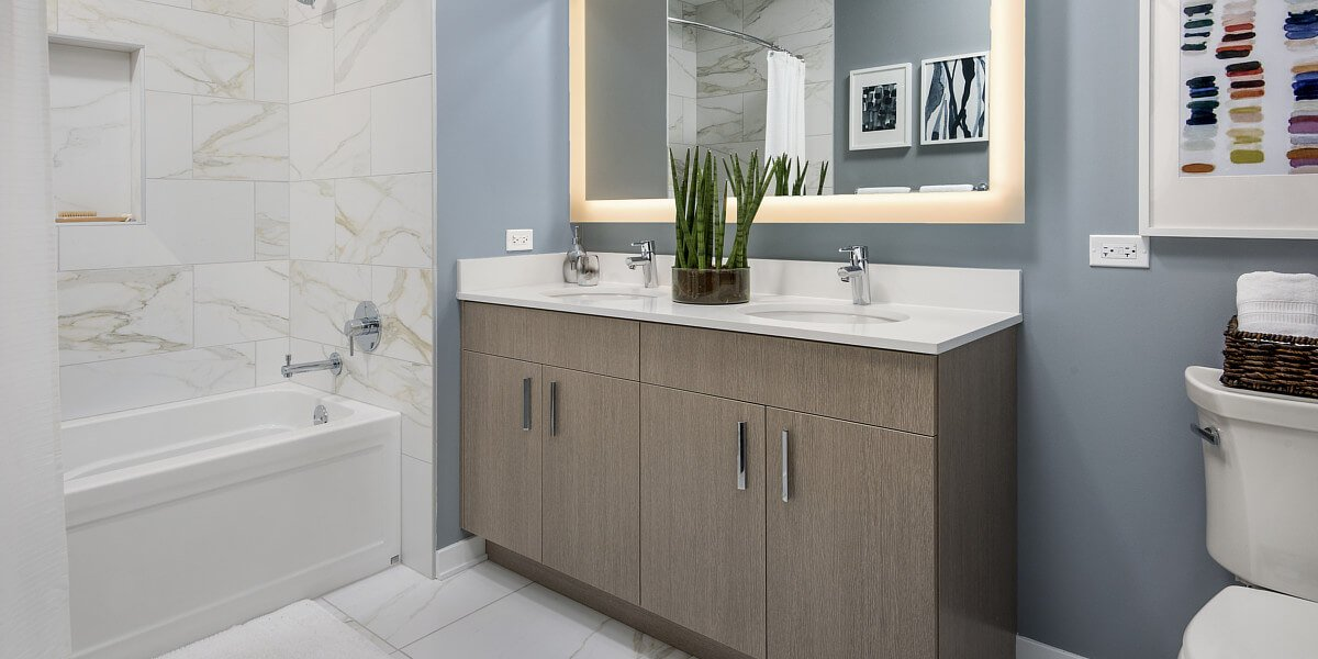 Sinclair bathroom featuring curtained bathtub with white marbled tiles, white double sink countertop, and tan cabinets