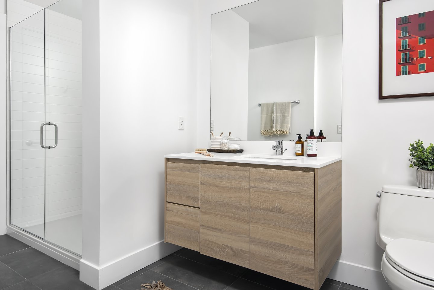 The Fields bathroom with white single sink counter, tan wooden cabinets, and glass shower stall with white tiles