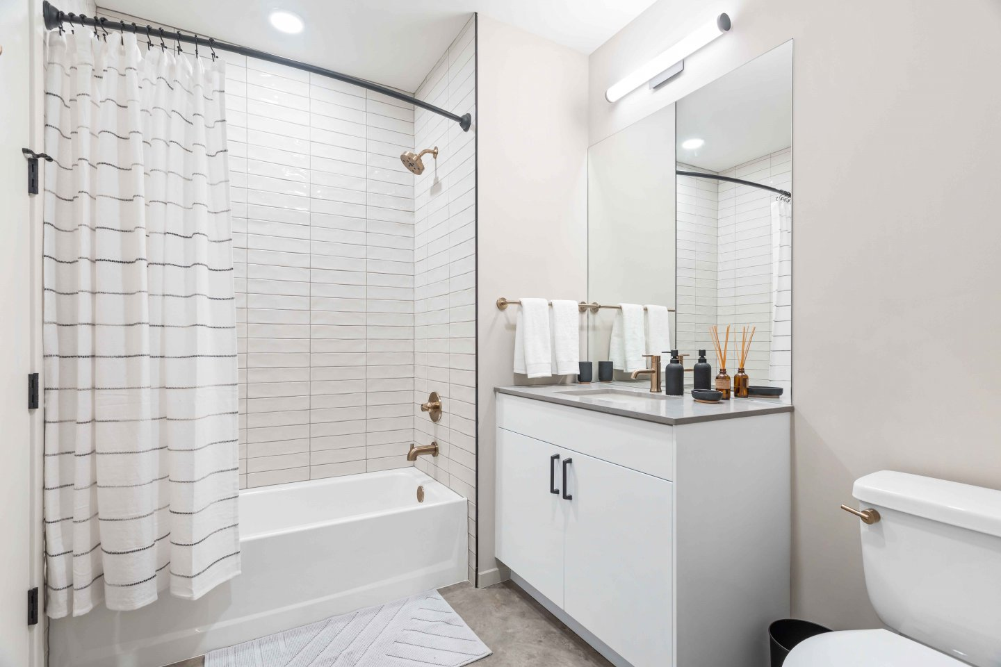 The Jax bathroom with white bathtub and tiles, white cabinets, and light grey single sink countertop
