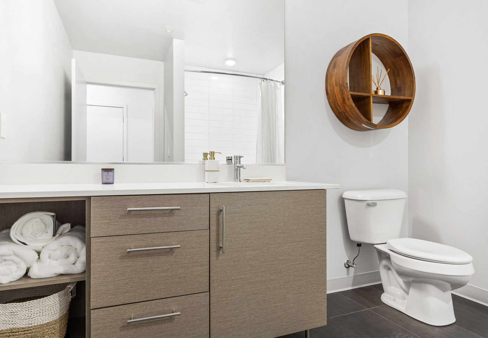 Upshore bathroom with white single sink counter, light brown cabinets, dark grey floor tiles